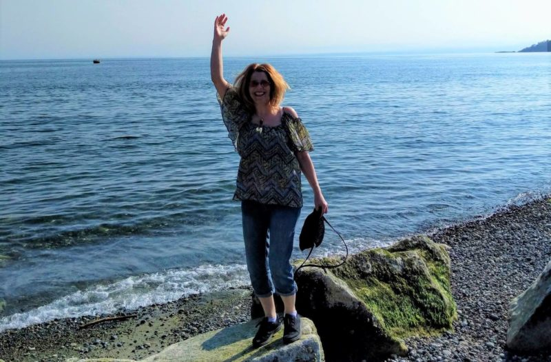 A photo of a woman standing on top of a rock by the ocean.
